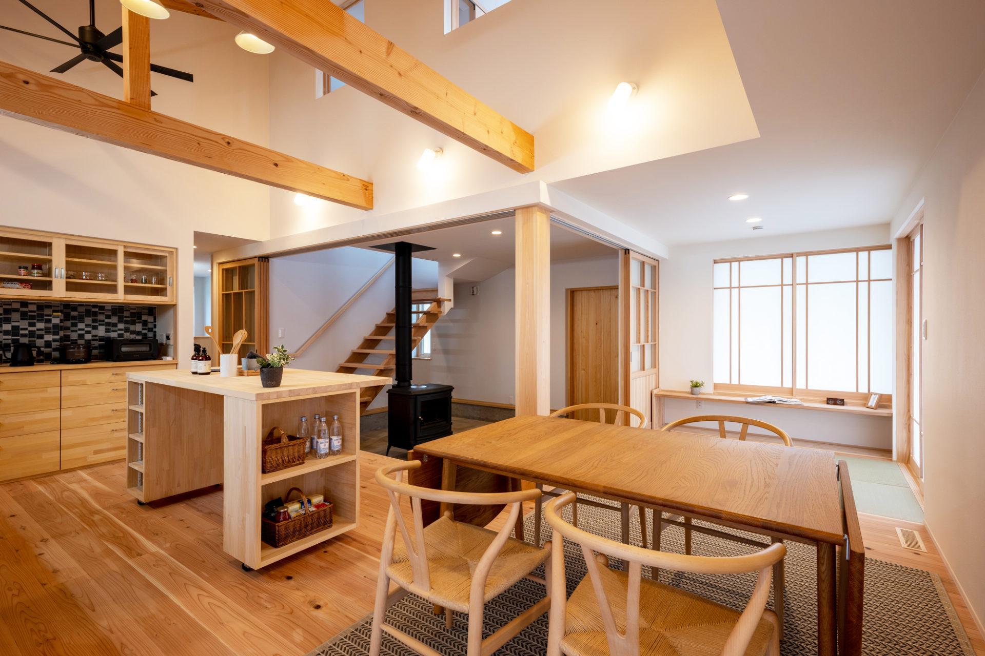 木製のキッチンとダイニングテーブルの奥に土間玄関と薪ストーブ